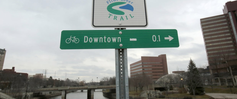 Image: A Flint River sign is seen along the Flint river in Flint, Michigan