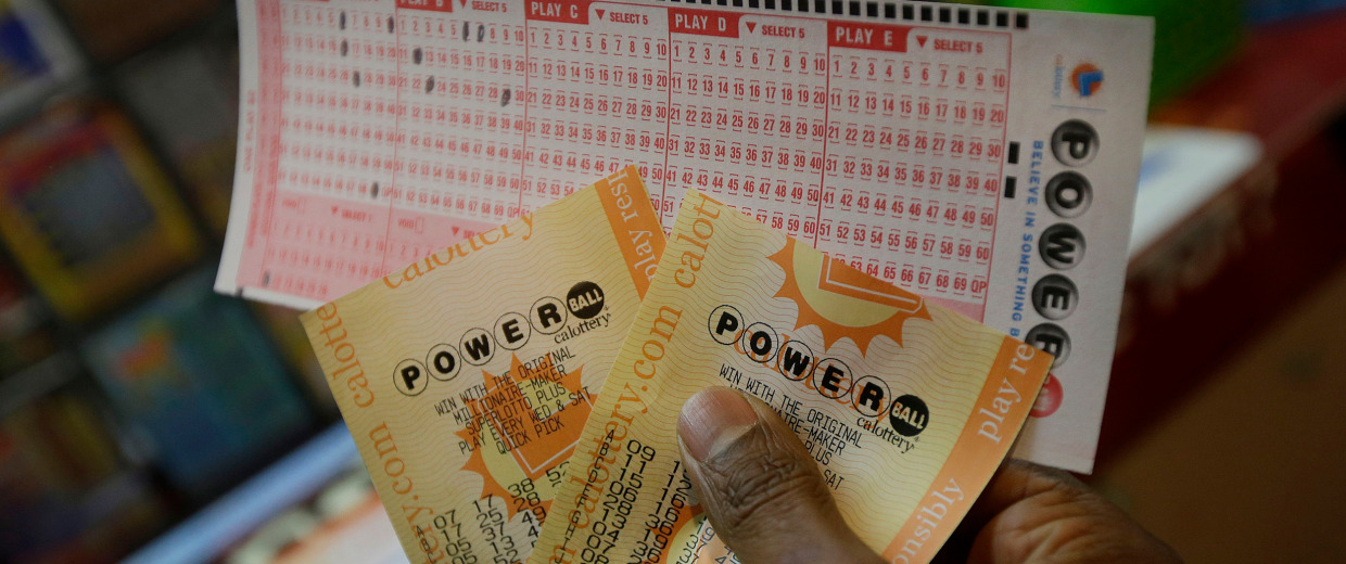 Image: A man holds up Powerball tickets he purchased