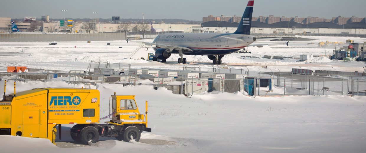 Image: A plane sits on the tarmac surrounded by snow at John F. Kennedy International Airport in New York