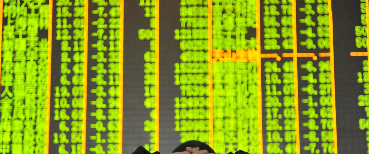Image: An investor looks at an electronic screen at a brokerage house in Hangzhou