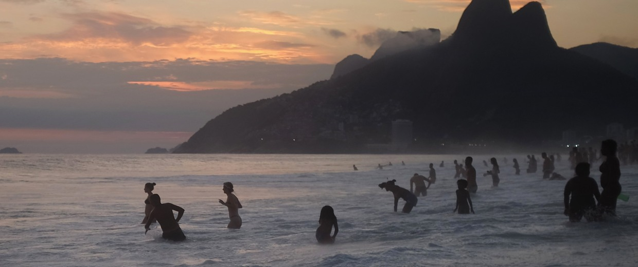 Image: Revelers bathe on Ipanema beach at sunset during Carnival celebrations