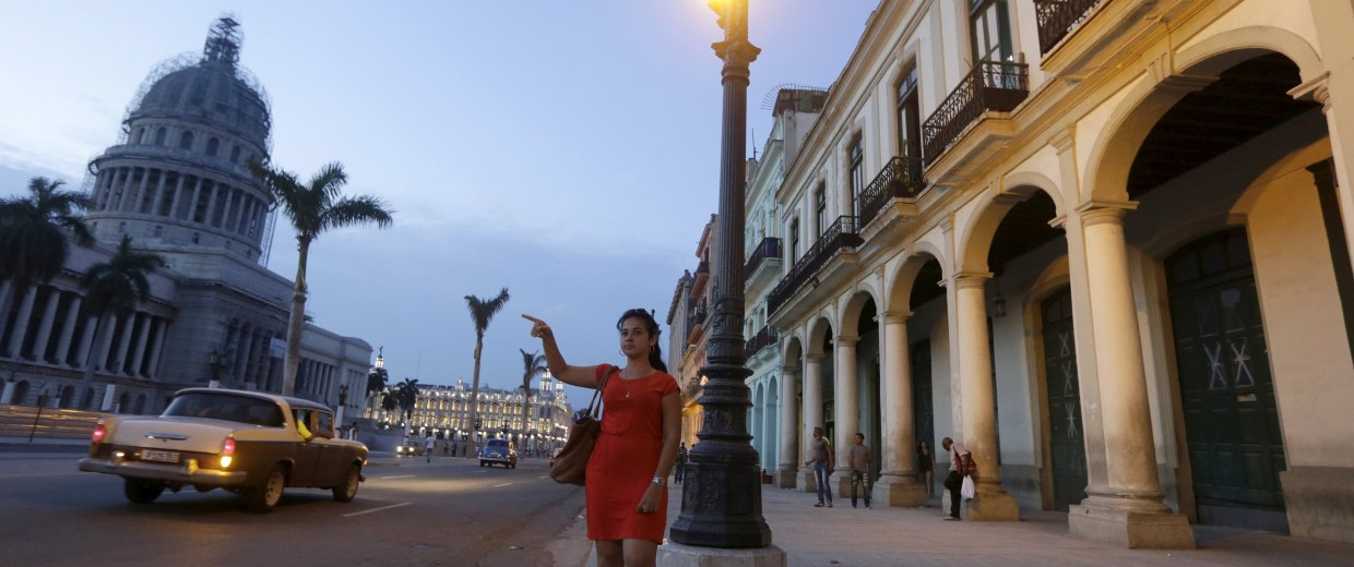 Image: A woman stops a taxi in front of the Capitol in Havana
