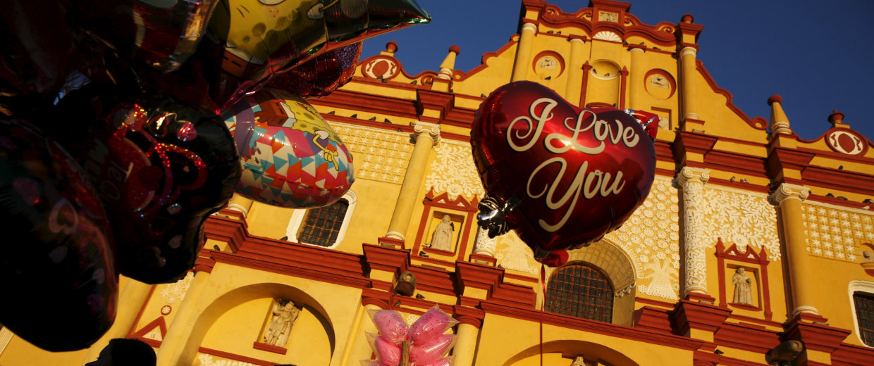 A girl looks at balloons in front of the Cathedral during Valentine's Day in San Cristobal de Las Casas.