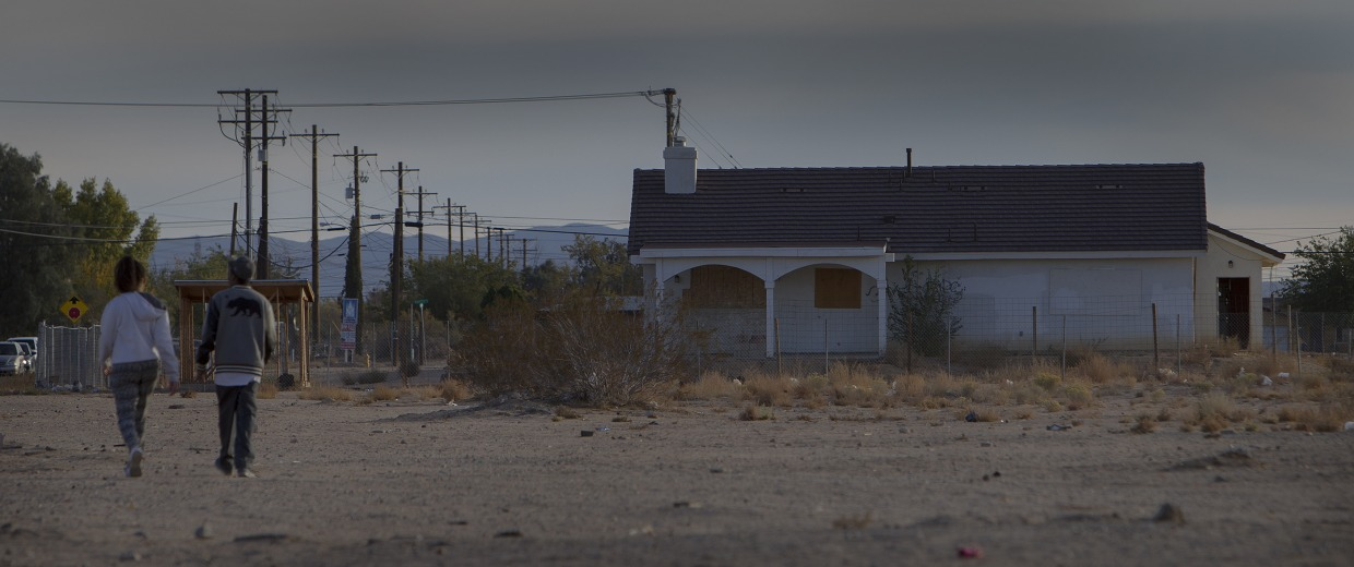 ADELANTO, CA - NOVEMBER 17, 2014: Youngsters walk through a dirt lot behind an abandoned home in the