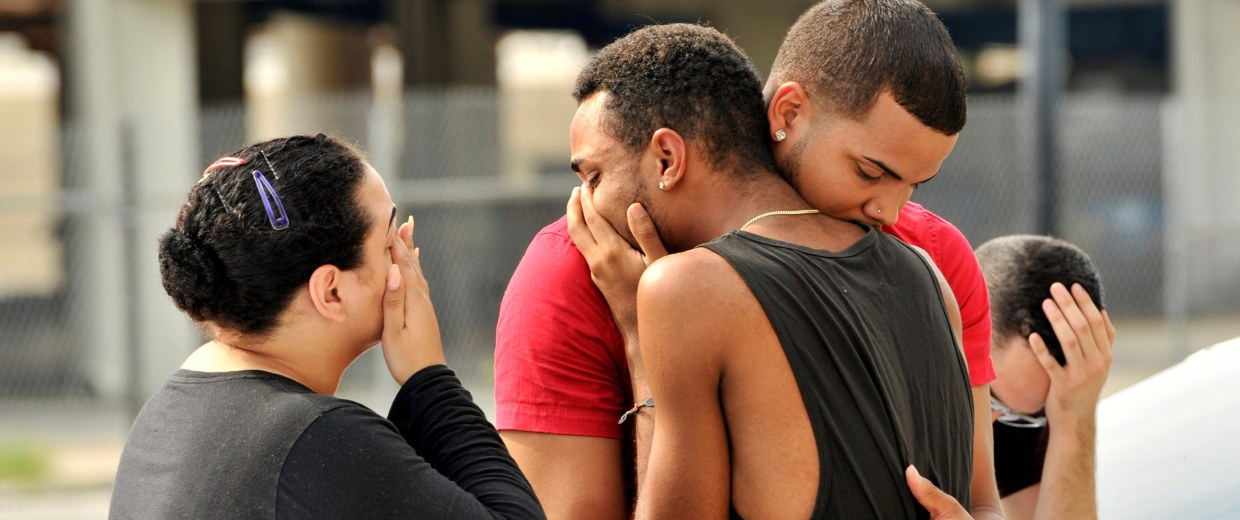 Image: Friends and family members embrace outside the Orlando Police Headquarters during the investigation of a shooting at the Pulse night club in Orlando, Florida