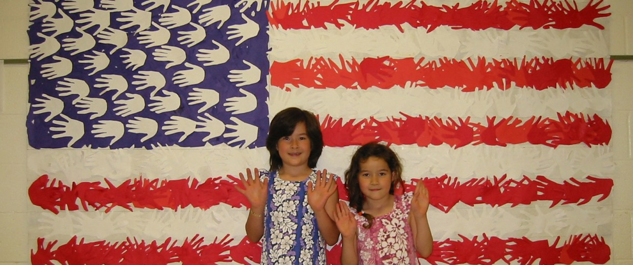 Frances Kai-Hwa Wang's daughters, M and Hao Hao, with an American flag made out of the handprints of all their schoolmates.