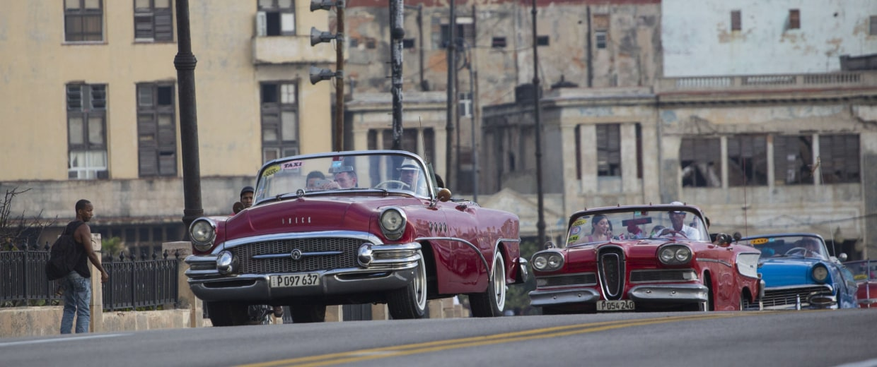 Fashion models are driven in vintage American convertible cars along the Malecon in Havana, Cuba.