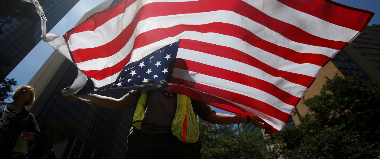 Image: A woman holds a U.S. flag during a prayer vigil in a park following the multiple police shooting in Dallas