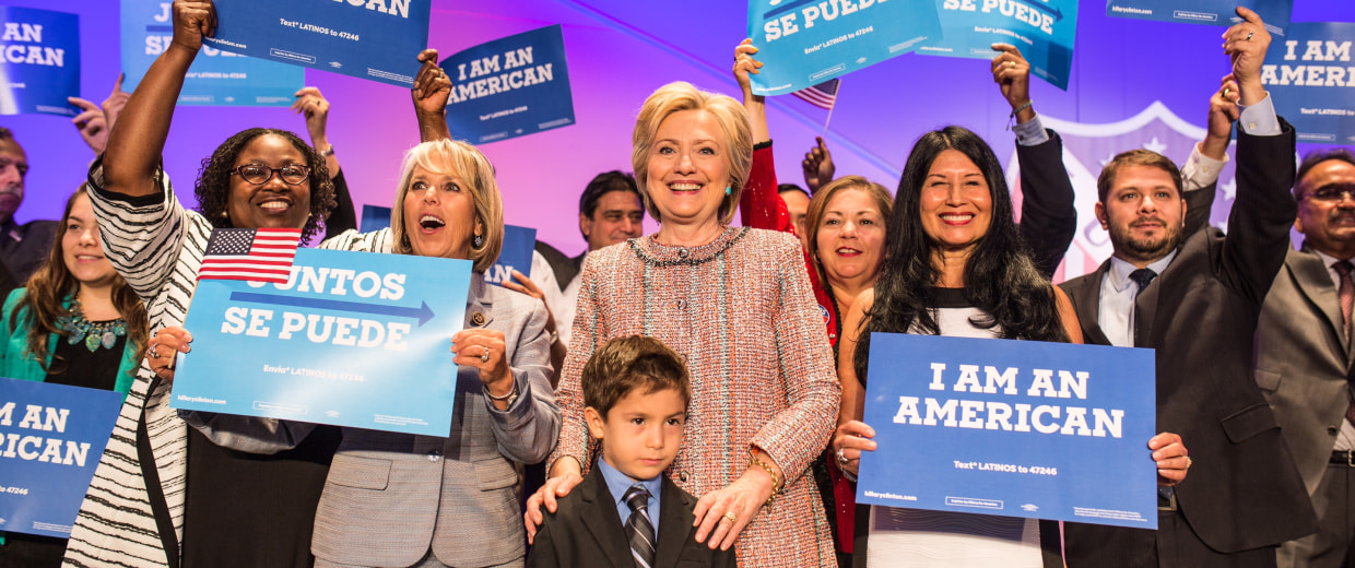 "Members of the Congressional Hispanic Caucus joined Hillary Clinton on stage after her LULAC speech and held reading "" I am an  American."""