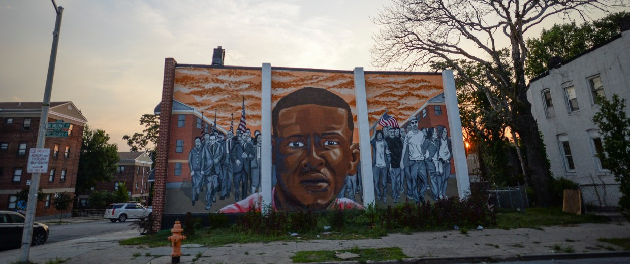 Image: The sun sets behind a mural of the late Freddie Gray in the Sandtown neighborhood of Baltimore, Maryland