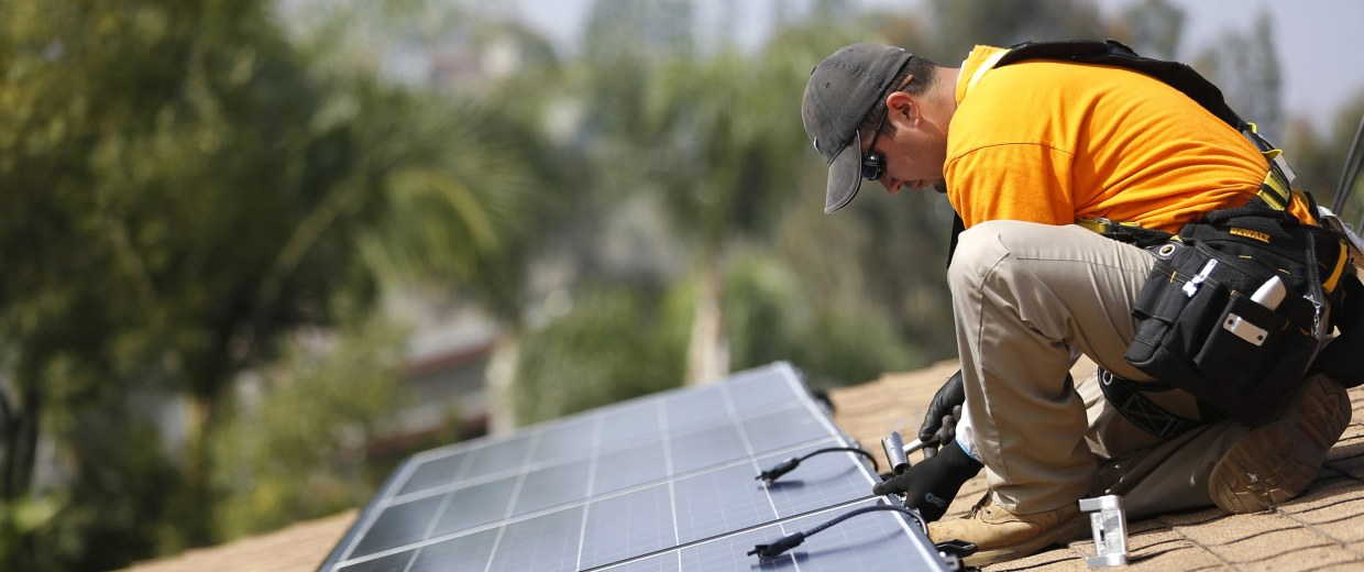 Image: Vivint Solar technician Aguilar installs solar panels on the roof of a house in Mission Viejo