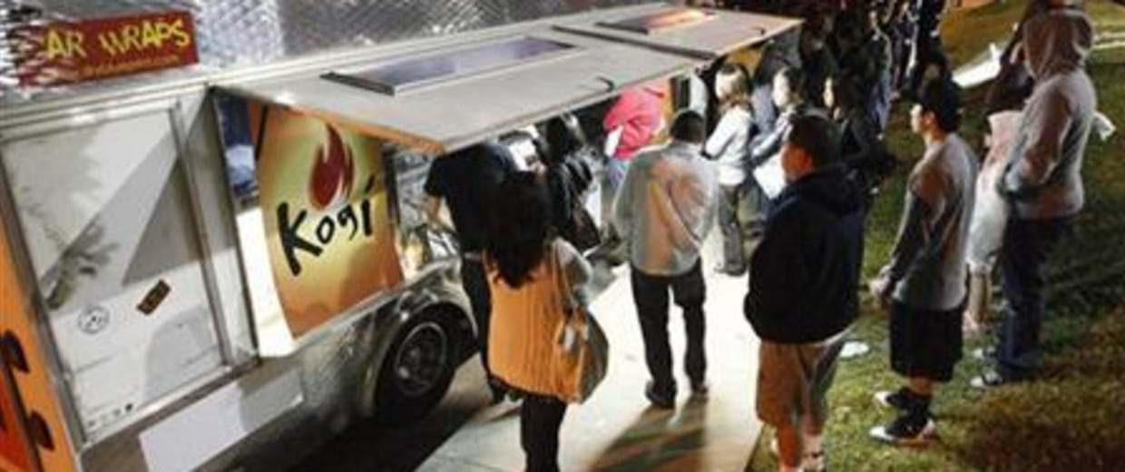 People wait for their food as others line up to place their orders at Kogi, a Korean BBQ-inspired taco truck, in Torrance