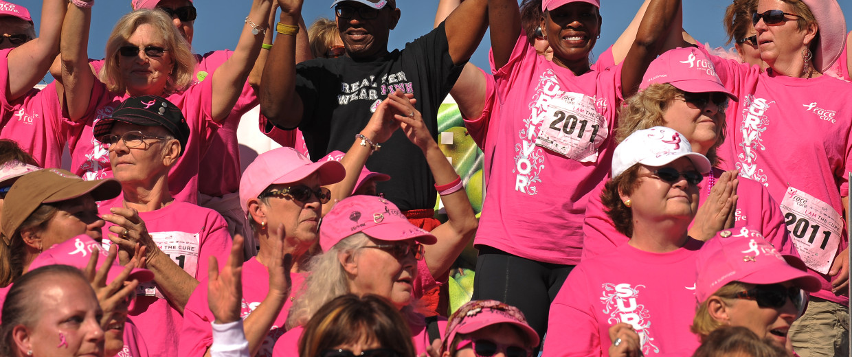 """Denver, CO., October 2, 2011- 6 year cancer survivor Saundra Robinson, second from right in back gets support from her husband Marcus during the Survivor Celebration Ceremony at the end of the race. The KOMEN DENVER Affiliate """"ignited the passionate"""" ath"""