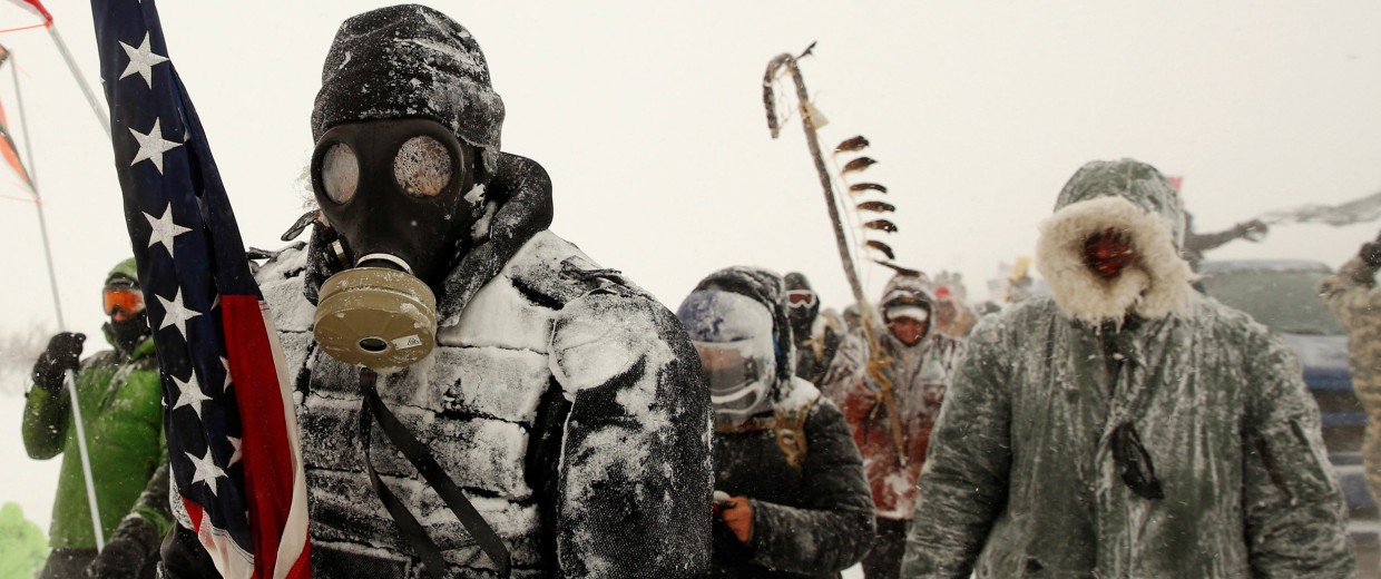 "Image: A man takes part in a march with veterans to Backwater Bridge just outside of the Oceti Sakowin camp during a snow fall as ""water protectors"" continue to demonstrate against plans to pass the Dakota Access pipeline"