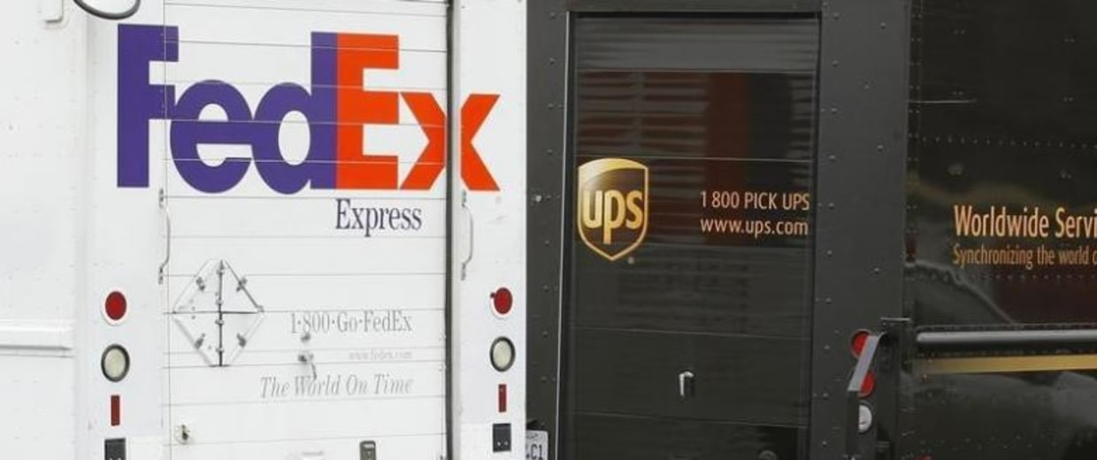 A FedEx truck is parked next to a UPS truck as both drivers make deliveries in downtown San Diego