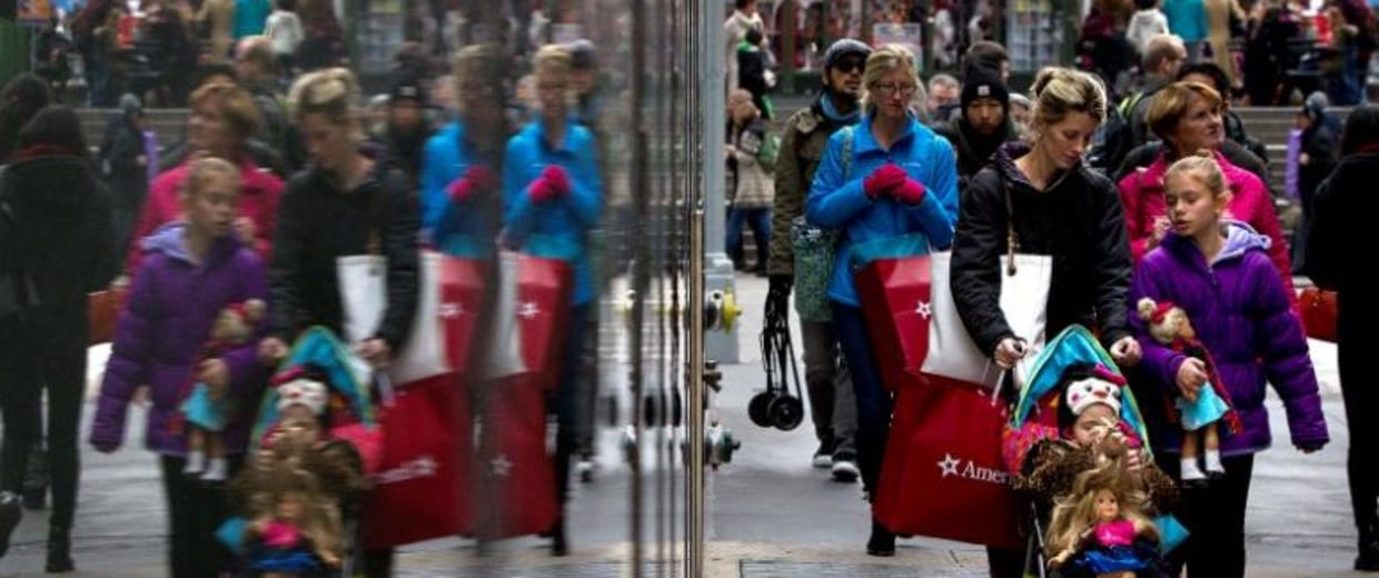 Shoppers are reflected in a window as they walk though Times Square in New York