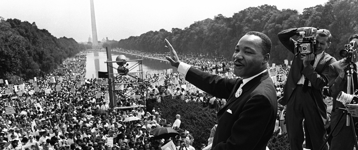 """Image: The civil rights leader Martin Luther KIng waves to supporters Aug. 28, 1963 on the Mall in Washington DC (Washington Monument in background) during the """"March on Washington""""."""