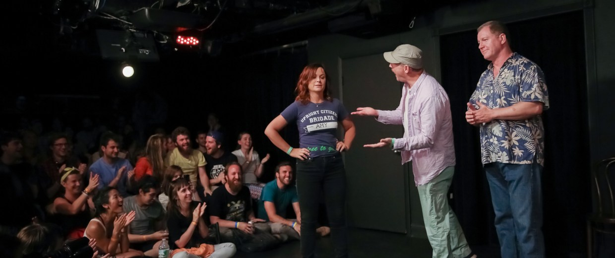 Image: Comedians Amy Poehler, Matt Walsh and Ian Roberts perform on stage at the Upright Citizens Brigade Theatre