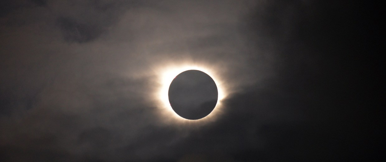 Image: A total solar eclipse is visible through the clouds as seen from Vagar on the Faeroe Islands, Friday, March 20, 2015.