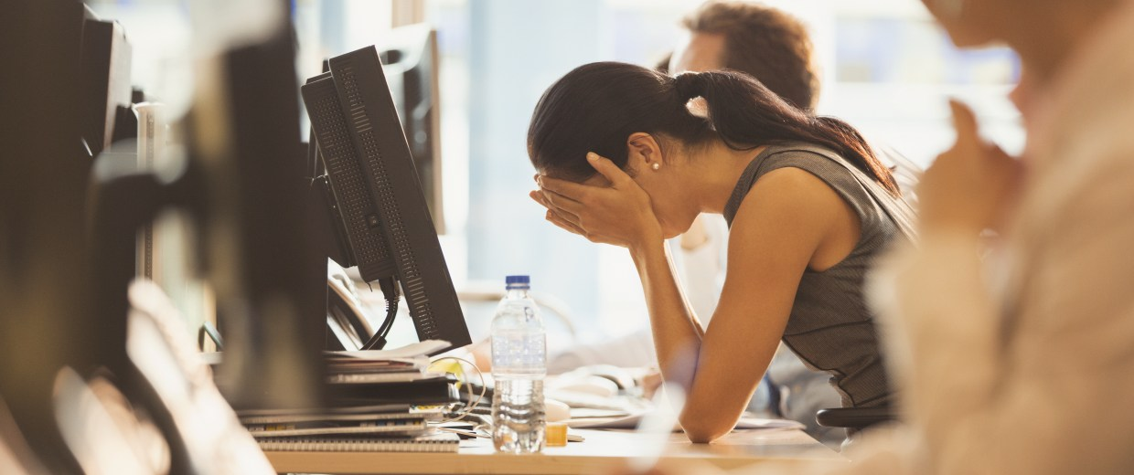 Image: Stressed businesswoman crying with head in hands at office desk