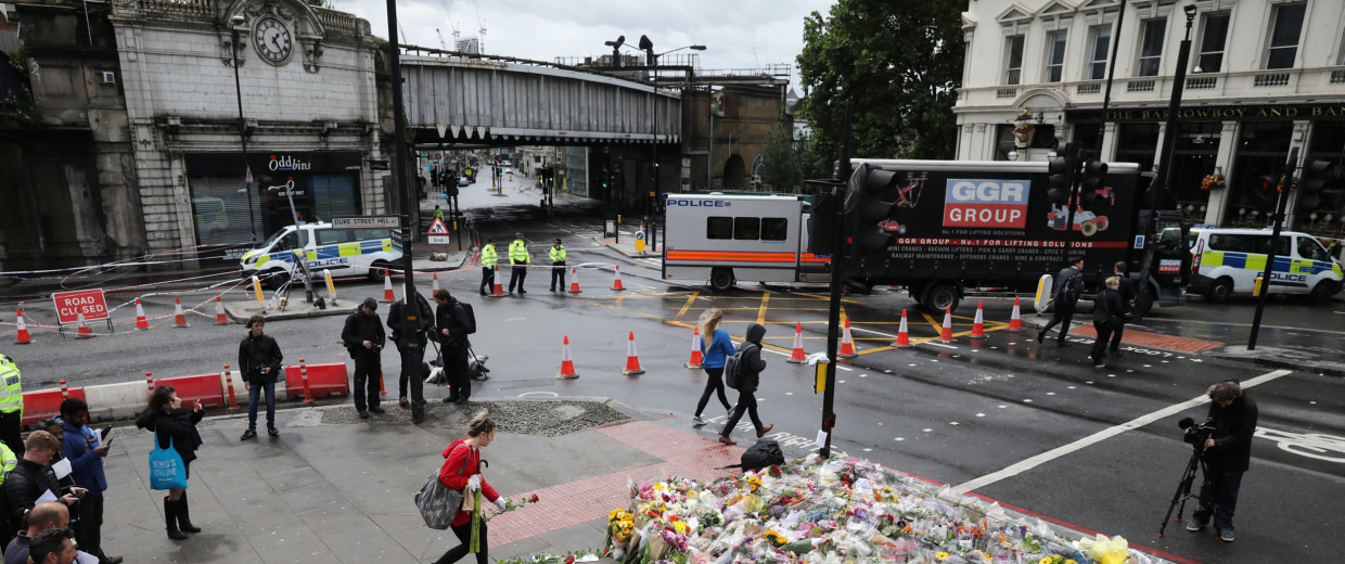 Image: A woman places a rose with other floral tributes for the victims of the attack on London Bridge and Borough Market at London Bridge, London