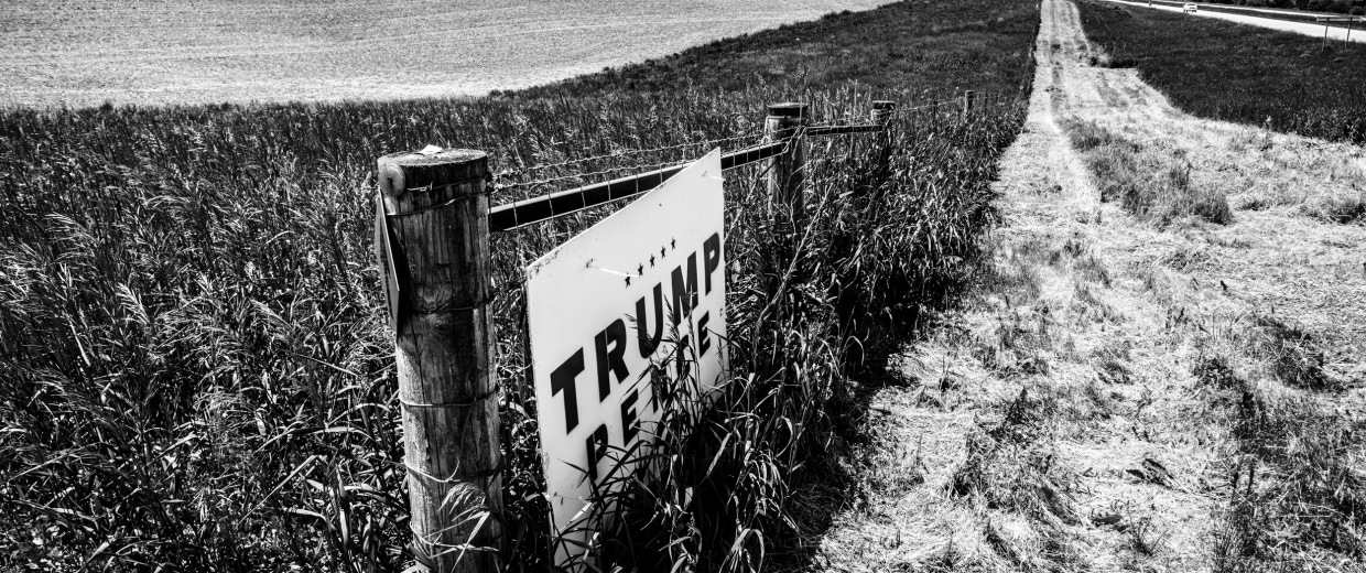 Image: A Trump Pence sign still hangs on a gate in a farm field.