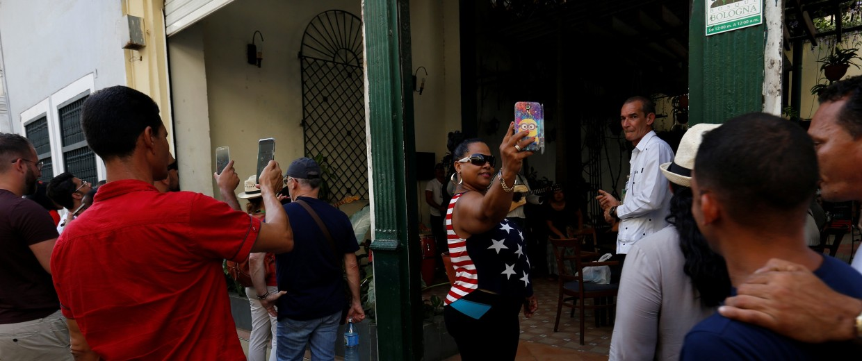 Image: Tourists take pictures in Havana