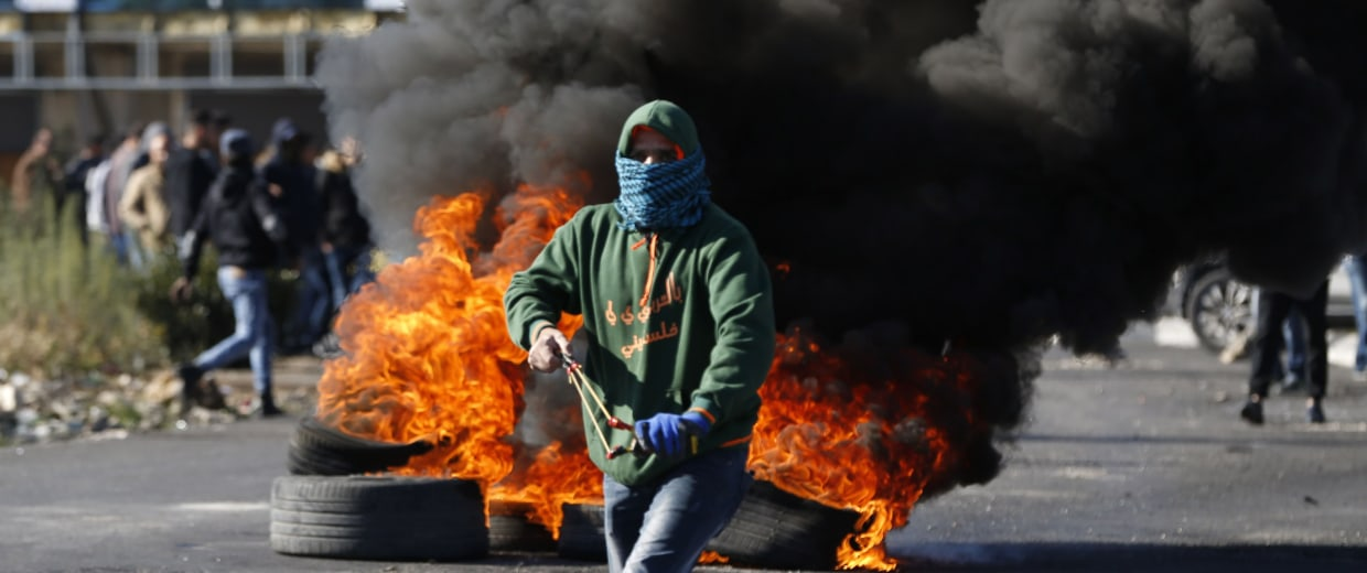 Image: A Palestinian armed with a slingshot attends a protest in Ramallah