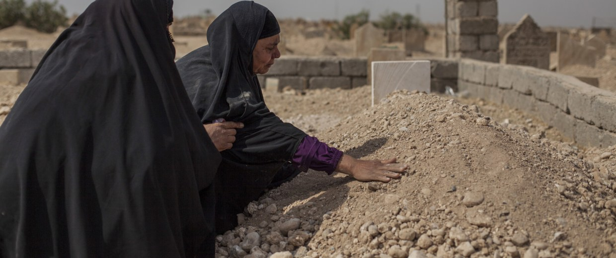 Image: Fatima Ahmed Aswad cries as she touches the grave of her 15-year-old daughter, Sana, in Mosul
