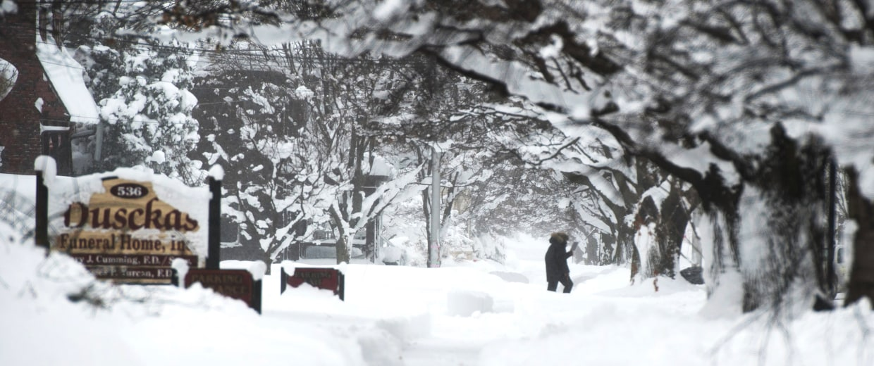 Image: A resident is out walking on 10th street after two days of record-breaking snowfall in Erie