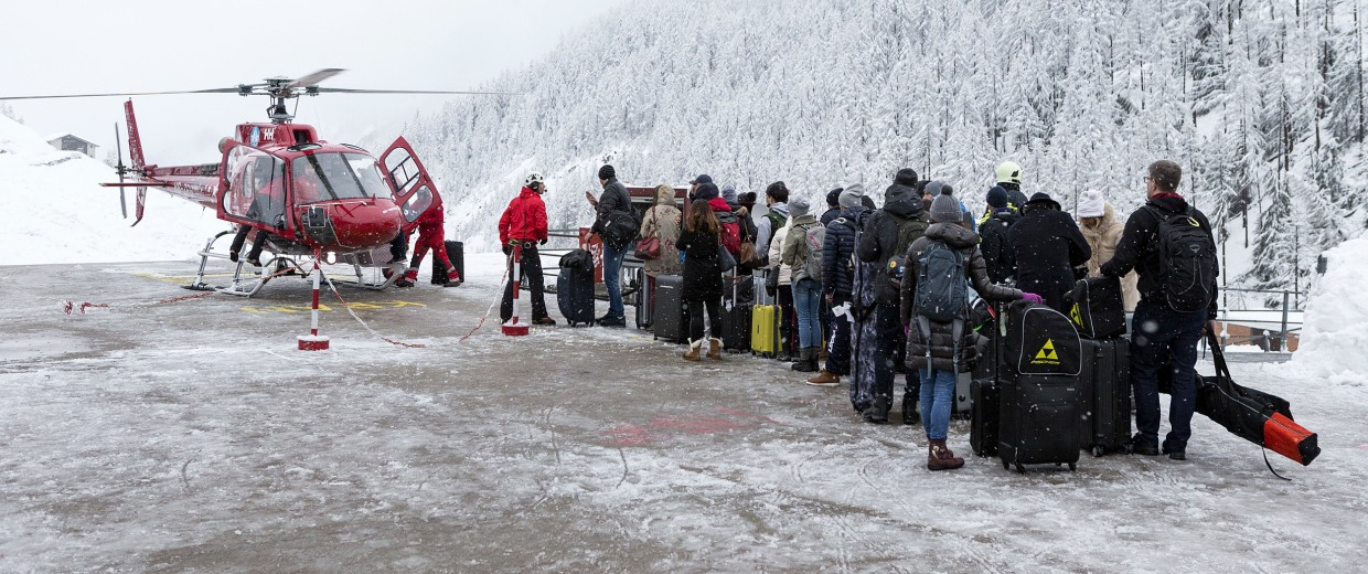 Image: Tourists wait in line at the heliport of Air Zermatt for a flight by airlift into the valley to Raron, in Zermatt