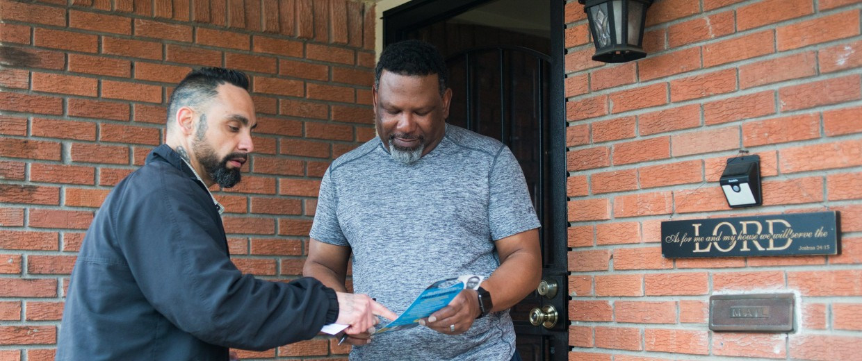 Image: William Roundtree, a campaign canvaser for the ACLU of Texas, speaks to Curtis Sanders as he goes door to door