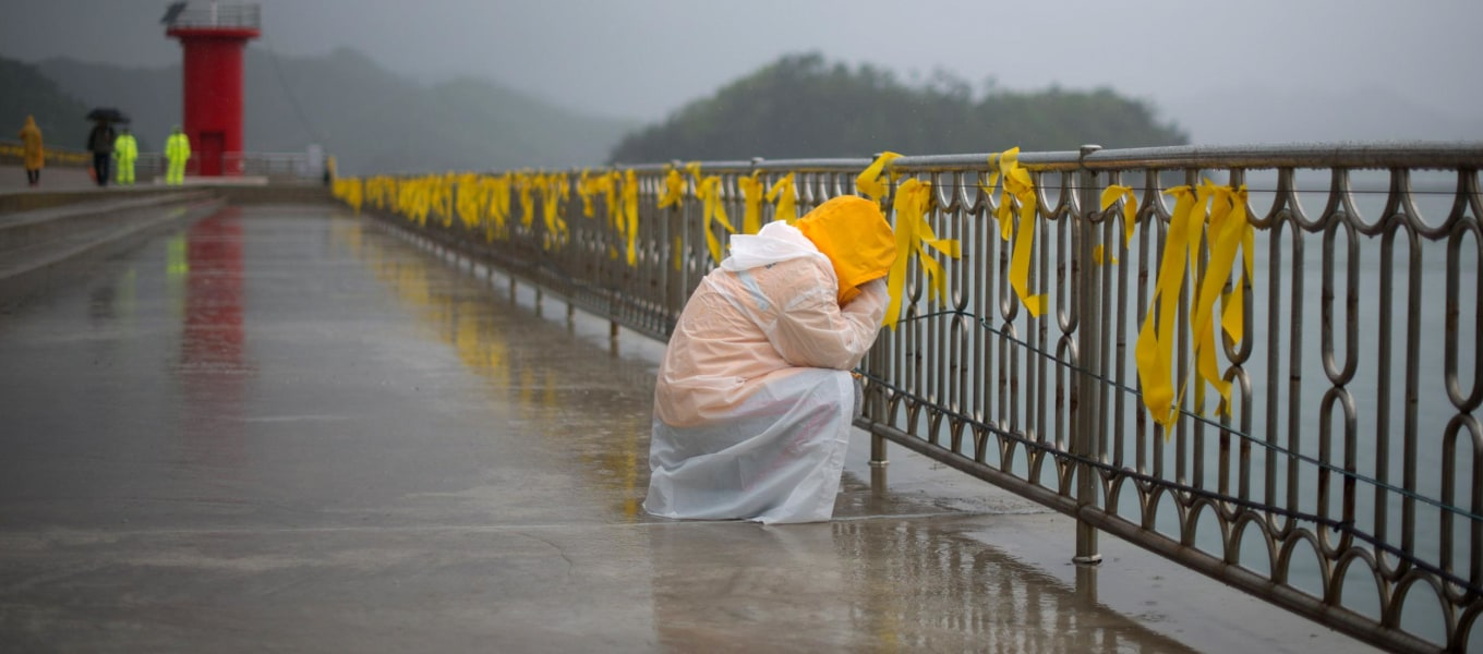 Image: A relative weeps before yellow ribbons at Jindo harbor