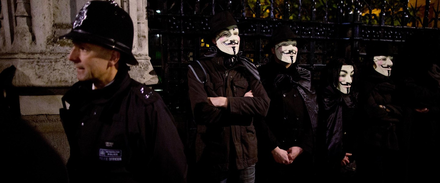 Anonymous supporters wearing Guy Fawkes masks stand beside a police officer at left as they take part in a protest outside Britain's Houses of Parliament in London, Monday, Nov. 5, 2012.