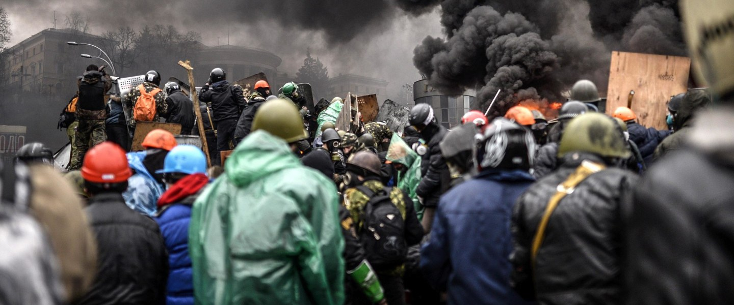 Image: Protesters gather behind barricades during clashes with police in Kiev.