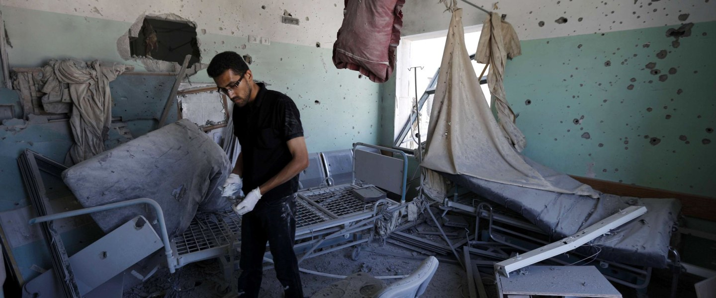 Image: A Palestinian employee inspects damages at the Al-Aqsa Martyrs hospital