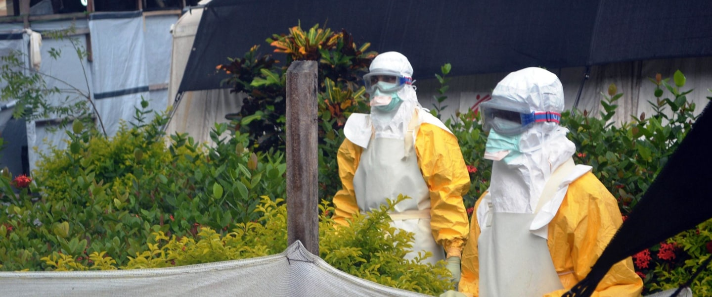 Image: Doctors Without Borders (MSF) personnel wearing protective gear walk outside the isolation ward of the Donka Hospital