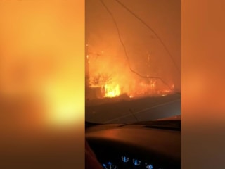Watch a father calm his daughter as they drive out of wildfire range