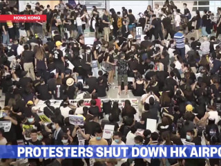 Thousands of protesters halt air travel in Hong Kong