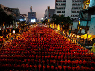 Thousands of Monks Flood Bangkok Streets for Alms Giving