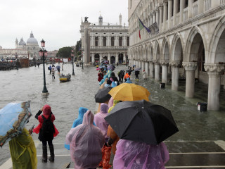 Tourists and residents slosh through a flooded Venice