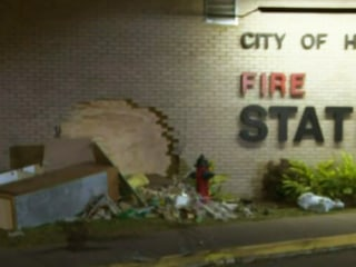 Driver crashes through brick wall of fire station, injuring firefighter