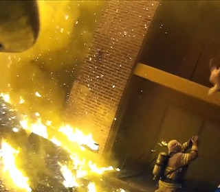 Firefighter makes perfect catch of a child thrown from burning building