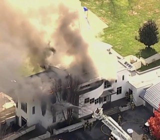 Brother charged with murder after family found dead in burning New Jersey mansion