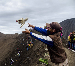 Worshippers Sacrifice Goods to Volcano's Crater