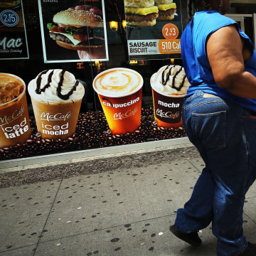 Image: A woman walks by a sign advertising sugary drinks