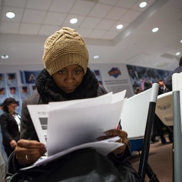 Image: A woman fills out paperwork at a job training and resource fair at Coney Island in New York