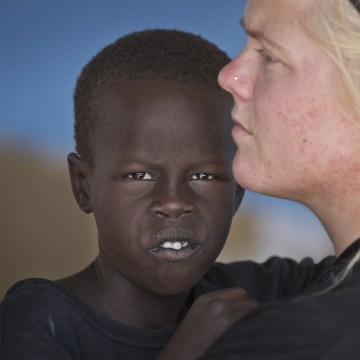 Image: American Katie Talbott, 23, holds one of the 10 orphans her mother Kim Campbell and stepfather Brad Campbell are raising