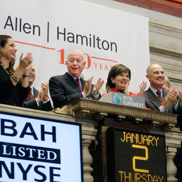 Image: Booz Allen Hamilton Chairman and CEO Ralph Shrader, center, and guests attend the opening bell ceremony at the New York Stock Exchange on Jan. 2.