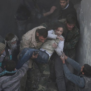 Image: Men help a wounded girl who survived what activists say was an airstrike by forces loyal to Syrian President Bashar al-Assad in the Duma neighbourhood of Damascus